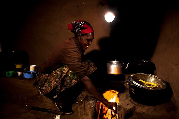 A Mother Cooking Using Solar Lantern For Lighting
