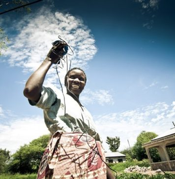 Tanzanian Woman Holds Up a Pay-As-You-Go Solar Device