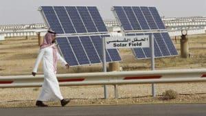A Saudi Man Walks on a Street past a Field of Solar Panels
