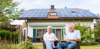Senior Man and Woman Sitting in Front of Their Solar-Roof House