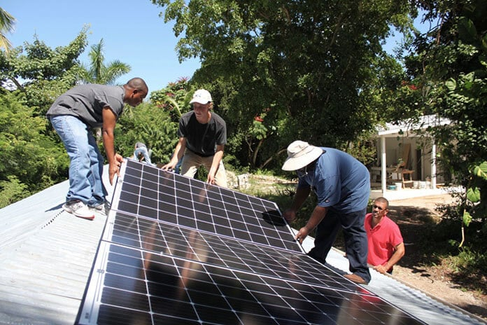 Bahamians Install Solar Panels on a Rooftop