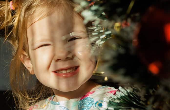 Little Girl Under Christmas Tree Seeking for Low-Carbon Christmas Decoration
