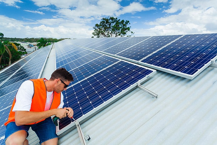 Young Solar Electrician Installing Solar Panels on a Roof
