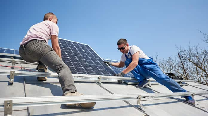 Electricians Mounting Solar Panels to Install the Solar System