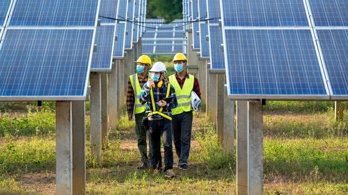 Solar Electricians Wearing Masks, Investigating Solar Arrays
