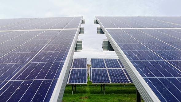 Réseaux de panneaux solaires, herbe verte et ciel bleu