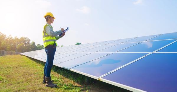 Engineer Inspecting Solar Panel Arrays